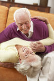 Romantic Senior Couple Lying On Sofa At Home Stock Image