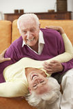 Romantic Senior Couple Lying On Sofa At Home Royalty Free Stock Photos