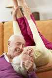 Romantic Senior Couple Lying On Sofa At Home Stock Images