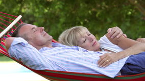 Romantic Senior Couple Relaxing In Garden Hammock Together stock video