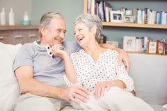 Romantic senior couple sitting on sofa in living room Stock Photography