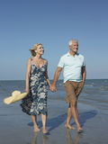 Romantic Senior Couple Walking On Beach royalty free stock photo