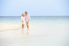 Romantic Senior Couple Walking On Beautiful Tropical Beach Stock Photos