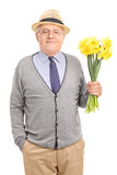 Romantic senior gentleman holding flowers Stock Photos