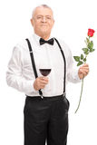 Romantic senior holding a glass of wine and a rose Stock Photography