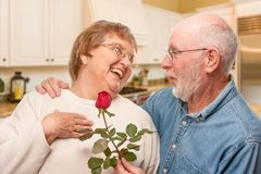 Romantic Senior Man Giving a Red Rose to His Wife. Happy Senior Adult Man Giving Red Rose to His Wife Inside Kitchen Royalty Free Stock Photos