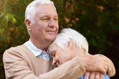 Romantic senior man warmly hugging his woman outside. Close up portrait of a senior men standing together in nostalgic hug with his wife while being outside in Stock Photo