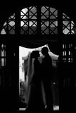Romantic, sensual newlywed couple silhouettes hugging in doorway Stock Photo