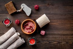 Floral foot spa with rose. Candles, salt, pumice stone, soap, buds on dark wooden background top view copyspace Stock Images