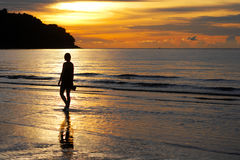 Romantic setting. Lady walking along beach during a sunset,she is bare footed and is silouetted against the sky Royalty Free Stock Image