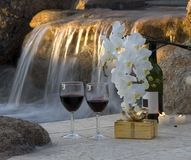 Romantic setting. Two wine glasses and a wrapped gift in front of a waterfall Stock Image
