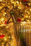 A romantic setting with a champagne bottle in front of a Christmas tree. royalty free stock images