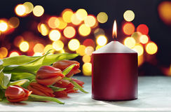 Romantic setting: red candle and tulips Royalty Free Stock Photos