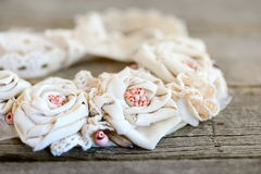 Romantic shabby chic necklace on a vintage wooden background. Beautiful flower necklace made of cotton fabric, lace ribbons Stock Photo