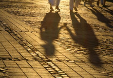 Romantic shadows. Soft aspect of the shadows of a couple hand in hand walking in a pavement square in the dusk lighting Stock Image