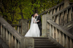 Romantic shot of newlywed husband and wife kissing on old stairc Stock Photography