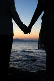 Romantic silhouette couple holding hands on a beach in sunset. Stock Photo