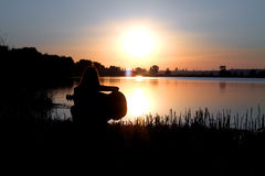 Romantic silhouette of the girl by the river playing guitar Stock Photo
