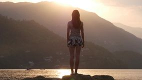 Romantic silhouette of a young woman on the shore stock footage