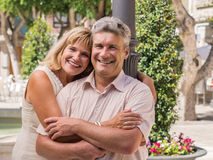 Romantic smiling mature healthy romantic middle-aged couple. Smiling mature healthy romantic middle-aged couple posing in a close affectionate embrace for a Stock Image