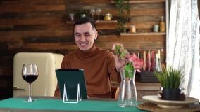 Romantic smiling young man presents beautiful flower through tablet to his girlfriend during online communication.