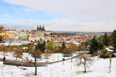 Romantic snowy colorful autumn Prague with gothic Castle Stock Photos