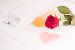 Romantic spa getaway. With red rose, heart shaped bath salts and soaps on luxurious white cotton bed linen Stock Photos