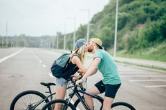 Romantic sports couple kissing against blurred background with bicycles. Beautiful young couple in love walking with bicycles, kissing and hugging. Stand near Royalty Free Stock Photos