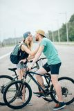 Romantic sports couple kissing against blurred background with bicycles. Beautiful young couple in love walking with bicycles, kissing and hugging. Stand near Royalty Free Stock Photography