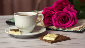 Romantic St Valentine`s setting with chocolate, tea cup and red roses Royalty Free Stock Photos