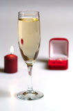 Romantic still-life. Candle, box with a gold ring and a champagne glass Stock Photography