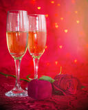 Romantic still life with champagne, gift box and red rose. On red background with bokeh in heart form. Marriage Proposal. Romantic Dinner: table place setting Stock Image