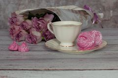 Romantic still life with a cup of coffee and marshmallows in a cozy ambience with roses royalty free stock image