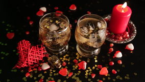 Romantic still life isolated on black background. Fire from candle shining and reflecting in glasses with alcohol drinks. stock video footage