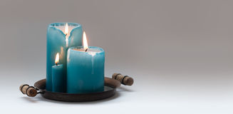 Romantic still life with turquoise different size candles on vintage metal plate. natural flame and drips. Beige Royalty Free Stock Images