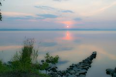 Romantic Stone dock, walkway in a lake at a sunset, Uveldy, The Urals, Russia royalty free stock photography