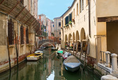 Quiet canal street in Venice. A romantic street cityscape of a quiet Venetian district with a canal and boats floating, a restaurant and ancient houses with Stock Image