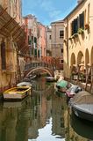 Quiet canal street in Venice. A romantic street cityscape of a quiet Venetian district with a canal and boats floating, a restaurant and ancient houses with Stock Photography