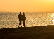 Romantic stroll along the beach at sunset couple Stock Images