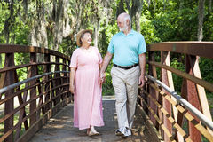 Romantic Stroll in the Park. Beautiful senior coule stays fit by walking together in the park Stock Image