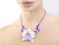 Romantic style: Fashion studio shot of beautiful woman with a fl. Polymer clay jewelery: beautiful woman with a floral orchid necklace around her neck, vintage stock photo