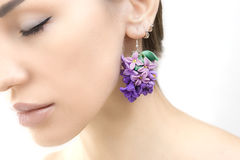 Romantic style: Fashion studio shot of beautiful woman with a fl. Polymer clay jewelery: beautiful woman with a lilac floral earrings, vintage accessories royalty free stock photo