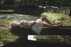 Romantic style young woman lie on small wooden bridge over pond. In tulle skirt and shirt with wreath of flowers in hair summer day Royalty Free Stock Photography