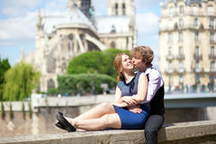 Romantic summer day in Paris. Couple of tourists sitting by Notre Dame Stock Photo