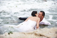 Romantic summer kiss (couple kissing). Beautiful couple kissing in the waves of the sea royalty free stock photos