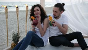 Romantic summer vacations for lovers guy and girl, tropics, couple with cocktails have fun at beach bungalow with white. Cloth, exotic vacation, background stock video footage