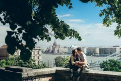 Romantic sunny portrait of the sensual couple in love tenderly rubbing noses while sitting on the balcony at the. Panorama view of Budapest, Hungary Royalty Free Stock Image
