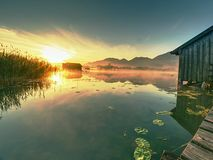 Romantic sunrise reflection on lake Kochelsee against boathouses. stock image