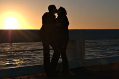 Romantic sunset. A couple is kissing each other near sunset. The sun is still shining so the couple is not more then a silhouet Royalty Free Stock Image