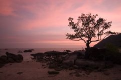 Romantic Sunset by the Beach. The sky glows in pink after sunset at the beach in Langkawi Island,Malaysia. Details include a couple sitting intimately together royalty free stock photography